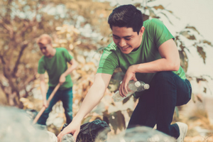 Image Of Two Young Men Cleaning Up Litter In The Woods