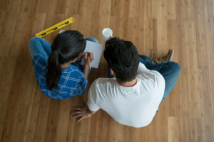Image Of Man And Woman Sitting On Floor Planning A Move
